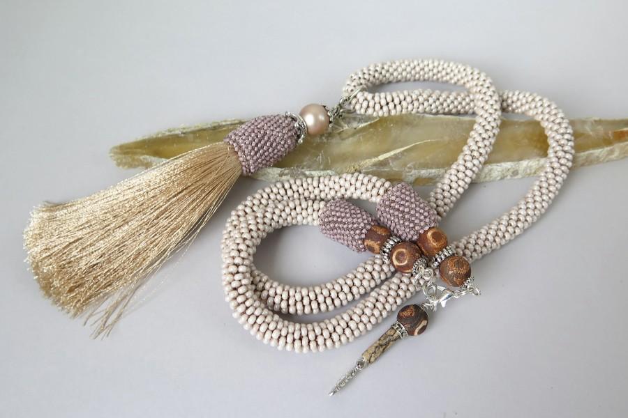 Smėlio spalvos kaklo papuošalas su kutu
